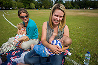 Two mothers breastfeeding their babies  while sitting on the grass in a local park during The Big Latch On annual awareness event.