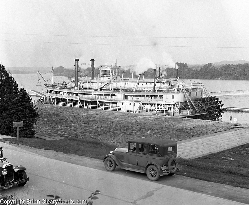 "The riverboat ""Queen City"" at a dock on the Ohio River , near U.S. lock # 18, with 2 old cars parked in the foreground in 1930's America.  (photo by bcpix.com)"