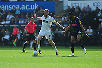Oli McBurnie of Swansea City vies for possession with Michael Ihiekwe of Rotherham United during the Sky Bet Championship match between Swansea City and Rotherham United at the Liberty Stadium in Swansea, Wales, UK.  Friday 19 April 2019