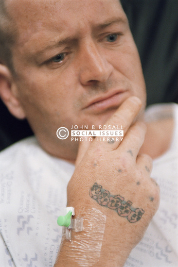 Man on drip with skull tattoos on his hand waiting to be seen in waiting room of hospital accident and emergency department,