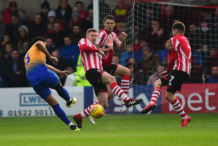 Lincoln City's Michael O'Connor blocks a shot from Mansfield Town's Jacob Mellis<br /> <br /> Photographer Andrew Vaughan/CameraSport<br /> <br /> The EFL Sky Bet League Two - Lincoln City v Mansfield Town - Saturday 24th November 2018 - Sincil Bank - Lincoln<br /> <br /> World Copyright © 2018 CameraSport. All rights reserved. 43 Linden Ave. Countesthorpe. Leicester. England. LE8 5PG - Tel: +44 (0) 116 277 4147 - admin@camerasport.com - www.camerasport.com