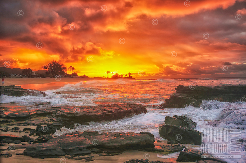Dramatic skies enhance the sunrise at Sandy Beach, O'ahu.