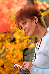 Redheaded woman listening to ipod, outside