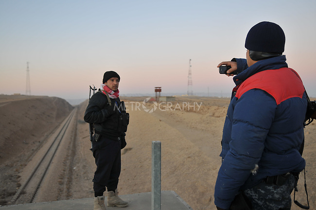 KIRKUK, IRAQ: Iraqi policemen take pictures of each other near railway lines during an anti-terror raid...After receiving intelligence about a terrorist training camp in the Hamria mountains, the Kirkuk Regional Police conduct a dawn raid...This is the first anti-terror raid in Kirkuk after the withdrawal of US troops...Photo by Pazhar Mohammad/Metrography