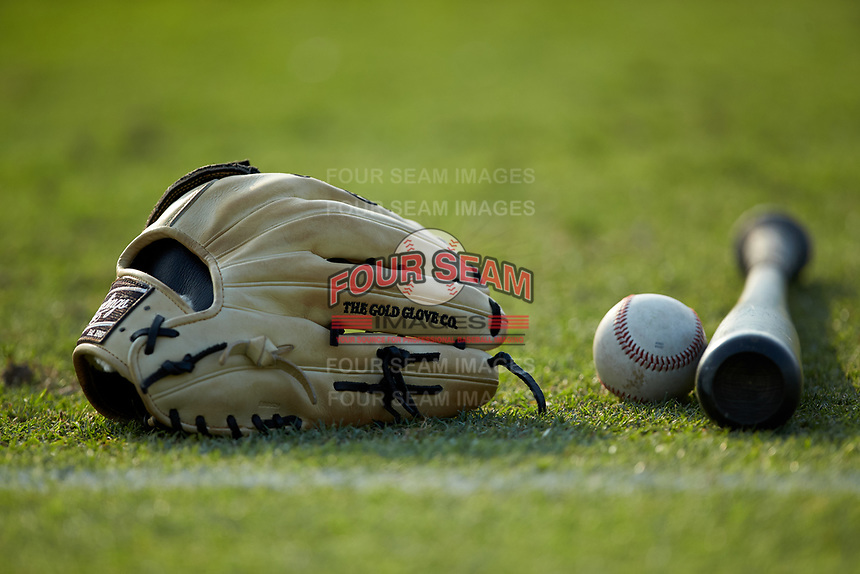 A Rawlings baseball glove sits on the outfield grass next to a baseball and a bat prior to the South Atlantic League game between the Delmarva Shorebirds and the Kannapolis Intimidators at Kannapolis Intimidators Stadium on June 4, 2019 in Kannapolis, North Carolina. The Intimidators defeated the Shorebirds 9-0. (Brian Westerholt/Four Seam Images)