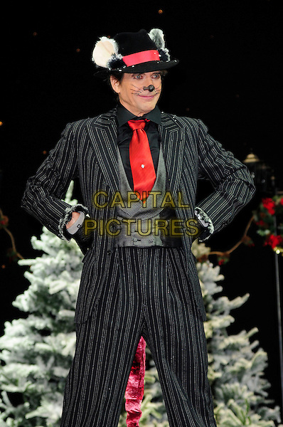 DIRK BENEDICT.First Family Entertainment theatre company's annual group Pantomime photocall at Piccadilly Theatre, London, England..November 26th, 2010.stage costume panto pantomime half 3/4 whiskers length black suit pinstripe hat red tie hands on hips nose.CAP/CAS.©Bob Cass/Capital Pictures.