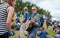 Happy boy that just arrived playing guitarr and singing. Photo: Christoffer Munkestam/Scouterna
