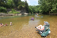 An adult keeps an eye on young swimmers at the Gar Hole swimming hole on the War Eagle River in southeast Benton County. It's a popular cooling off spot for people who live in and around Hindsville. <br />(NWA Democrat-Gazette/Flip Putthoff)