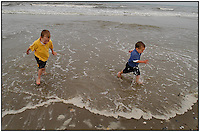 Two boys run along the beach on Ocracoke, N.C. in the North Carolina Outer Banks. Image is model released and can be used to illustrate other locations.