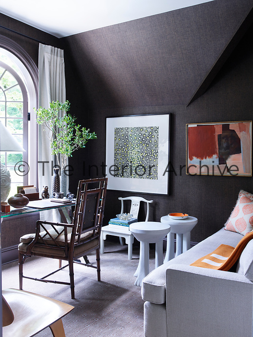 The study is decorated in tones of grey and has a cane chair and glass topped table set in front of the window. Pieces of modern art hang on the walls and there is a comfortable sofa against one wall.