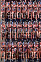 Portalhubwagen beim Eurogate im Hamburger Hafen: EUROPA, DEUTSCHLAND, HAMBURG, (EUROPE, GERMANY), 26.09.2016 Der Portalhubwagen (oder Portalhubstapelwagen oder Portalstapelwagen; engl. van carrier, straddle carrier, gantry lift ist ein spezielles Umschlaggeraet fuer ISO-Container. Es wird als Transportfahrzeug auf Containerterminals in Haefen eingesetzt.<br />  <br /> Der Portalhubwagen besteht aus einem Rahmengestell und einer dazwischen haengenden Hubvorrichtung Topspreader, das mit Hubwinden vertikal bewegt werden kann. Das Rahmengestell ist mit einem Fahrwerk mit meist acht Raedern ausgestattet. Die Fahrerkabine ist oben an einer Stirnseite des Rahmens angeflanscht.<br />  <br /> Der Portalhubwagen faehrt ueber einen Container, der auf dem Boden oder auf einem Lkw steht, der Spreader verriegelt sich hydraulisch gesteuert mit den vier Eckbeschlaegen des Containers und hebt diesen an.