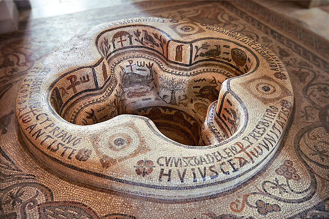 "Eastern Roman Byzantine walk in baptismal font from the 6th century AD Parish Church of Demna near Kalibia, Cape Bon, Tunisia. <br /> <br /> The baptismal font was removed from the church and restored in the Bardo Museum Tunis in 1955. <br /> <br /> The mosaic iconographic decorations represent the salvation of the neophyte, newcomer, who by being baptised is admitted into the Church of Christ whilst being illuminated by faith, represented the mosaic lit candle illustrations.<br /> <br /> The P with a cross through it is the Chi Rho, a Christian symbol which represent the first two letters of Jesus Christ's name in Greek. The Christogram also has the Greek letters Alpha and Omega which represent the passage from the book of revelations: ""I am the Alpha and Omega"" Chapter 1 verse 8, which is clarified by ""the beginning and the end"" (Revelation 21:6, 22:13). <br /> <br /> In these type of baptismal fonts those being baptised would have been fully immersed in water as John the Baptist immersed Jesus. <br /> <br /> The font was paid for by donation by Iuliana and Aquinius who dedicated the font to St Cyprian, the martyed Bishop of Carthage, circa 258,  and the author of a treatise on baptism rites<br /> <br /> The Bardo Museum Tunis"