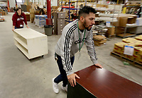 Neako (cq) Ramos, a volunteer, helps move recently donated office furniture Tuesday, February 11, 2020, at the Habitat for Humanity ReStore of Washington County in Fayetteville. The store, that is open Tuesday through Saturday. Check out nwaonline.com/200212Daily/ and nwadg.com/photos for a photo gallery.<br /> (NWA Democrat-Gazette/David Gottschalk)