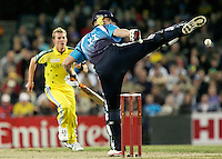 England batsman Andrew Flintoff kicks out at a ball from Australian bowler Brett Lee