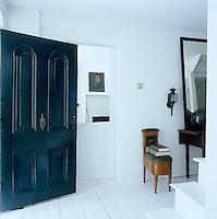 The massive black-painted front door standing open; next to it the kitchen can be seen through a half-open stable door