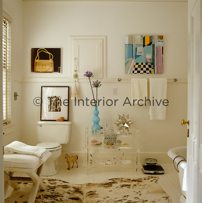 A collection of artworks is displayed in the all-white master bathroom which is furnished with a vintage lucite table and calfskin rug