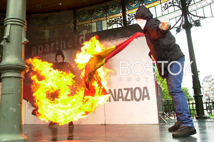 "Hooded people burn a Spanish flag during a demonstration with the slogan ""No Apartheid, Self determination"" on 19 August, 2003 in Donostia-San Sebastian, Basque Country. (Ander Gillenea / Bostok Photo)"