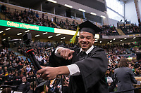 Chidiebere Iwuoha Jr., B.B.A. Management, films himself walking to receive his degree during UAA's 2019 Spring Commencement at the Alaska Airlines Center.