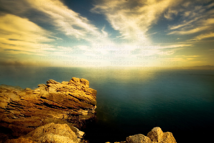 A rocky shore with calm water