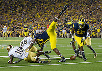 Wide receiver DaVaris Daniels (10) and wide receiver Corey Robinson (88) fall to the ground as Michigan Wolverines tight end Devin Funchess (87) and defensive back Blake Countess (18) break up a hail mary pass at the end of the second quarter.
