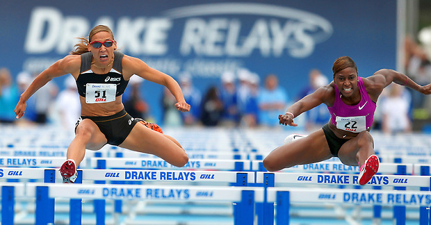 Lolo Jones of ASICS, left, clears the second to last hurdle in the women's 100 meter hurdles special Saturday at the Drake Relays. She was narrowly edged out by Nike's Damu Cherry of Nike, at right.