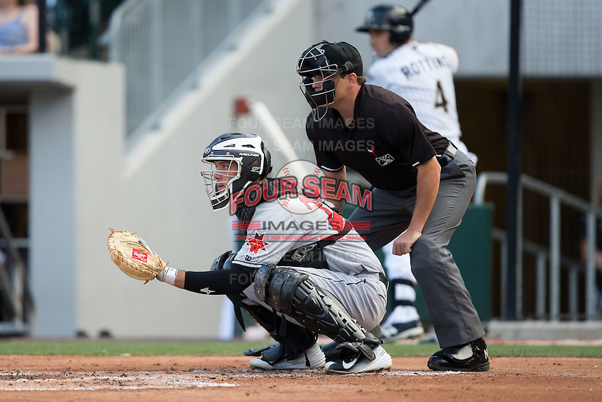 Indianapolis Indians catcher Jacob Stallings (23) sets a target as home plate umpire Jansen Visconti looks on during the game against the Charlotte Knights at BB&T BallPark on June 17, 2016 in Charlotte, North Carolina.  The Knights defeated the Indians 4-0.  (Brian Westerholt/Four Seam Images)