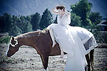 A young woman wearing a long white dress  sitting on a horse