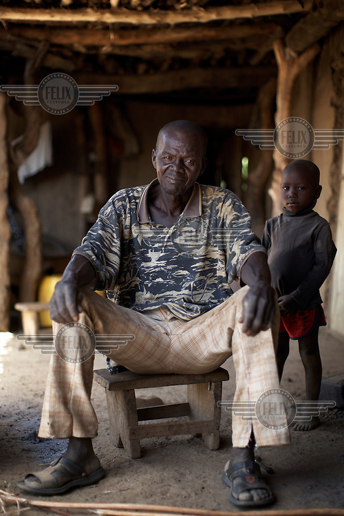 Farmer Stephen Ollo, 62, and his grandson Clifford, 3, pictured at their home.