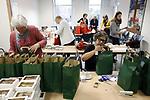 Foto: VidiPhoto<br /> <br /> ZETTEN – Leden van vrouwenverenigingen uit Andelst, Randwijk, Valburg en Zetten pakken woensdag in gebouw De Hoeksteen in Zetten honderden kerstpakketten in voor Poolse en Roemeense arbeidsmigranten in de Betuwe. Dit jaar zijn dat er 950 stuks, meer dan voorgaande jaren. De Polen en Roemen zijn vooral werkzaam bij boomkwekers, in de fruitteelt en in de (bloemen en planten) kassen. In het Kerstpakket zit dit jaar naast evangelisatiemateriaal en een Betuwse Kerstgroet, onder andere ook een chocoladeletter van een Betuwse bakker en een zakje met Nederlandse bloembollen (voorzien van gebruiksaanwijzing in de eigen taal). Dit jaar zijn er voor het eerst ook pakketten voor Roemeense werknemers, omdat daar steeds meer arbeidsmigranten vandaan komen, met name uit Moldavië. De kerstpakketten worden de komende weken verspreid door diverse werkgevers onder hun personeel. Kerst vieren de werknemers vrijwel allemaal in eigen land.
