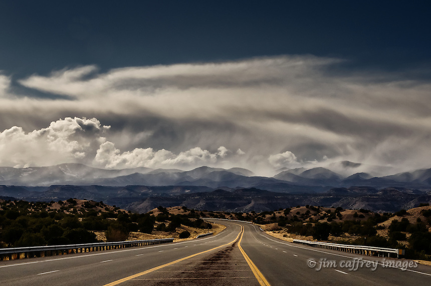 New Mexico Highway 502 in San Ildefonso Pueblo leading to the Jemez Mountains, which are hidden by storm clouds.