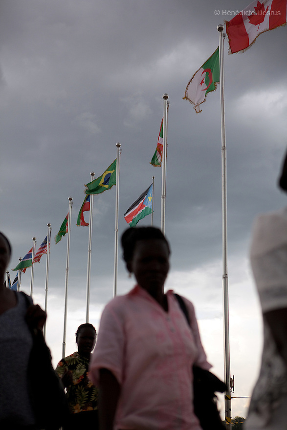 july 19, 2011 - Juba, Republic of South Sudan - South Sudaneses walk by the new Republic of South Sudan flag and other countries flags at the Dr John Garang Mausoleum in the capital city of Juba. Tens of thousands of South Sudaneses celebrated national independence on july 9, 2011, but whether statehood will resolve issues of identity after a decades-long war remains to be seen. The Republic of South Sudan became a United Nations member state and the world's 193rd country. Photo credit: Benedicte Desrus