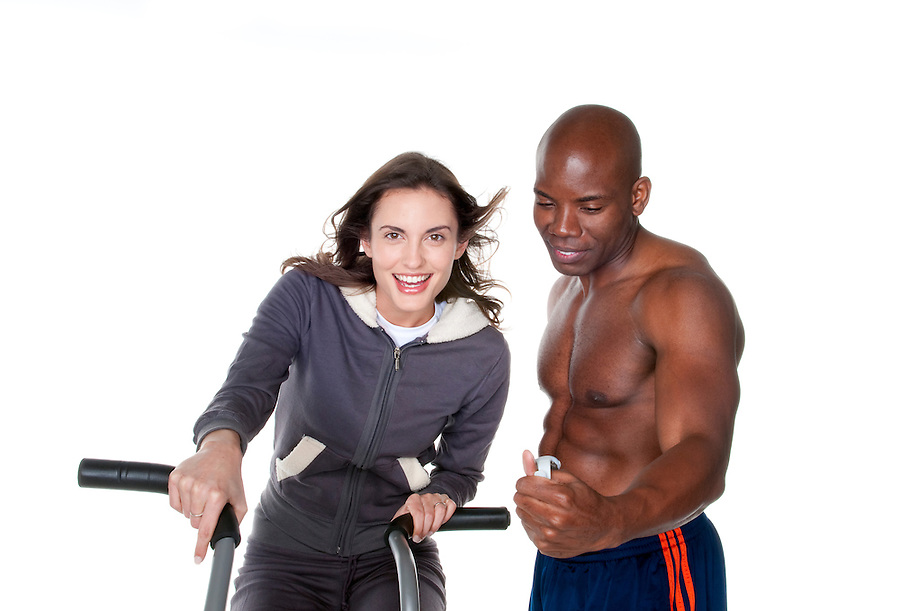 Young caucasian woman trainning in the gym with personal trainer.