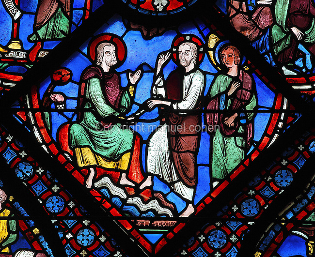 On the rocky shore of Galicia, Christ, walking on the water, blesses James and hands him a stick representing his mission to convert Spain. Section of Christ giving a stick to St James, 1210-25, from the Life of St James window in the ambulatory of Chartres Cathedral, Eure-et-Loir, France. This window tells the story of the life of St James the Greater, apostle of Jesus and son of Zebedee. It is situated next to the apostles chapel. Chartres is a stop on the pilgrimage route to Compostela, where James' relics lie. Chartres cathedral was built 1194-1250 and is a fine example of Gothic architecture. Most of its windows date from 1205-40 although a few earlier 12th century examples are also intact. It was declared a UNESCO World Heritage Site in 1979. Picture by Manuel Cohen