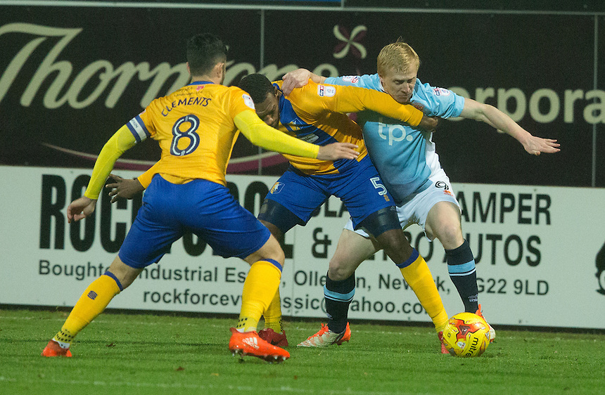 Mark Cullen of Blackpool battles with Krystian Pearce and Chris Clements of Mansfield Town<br /> <br /> Photographer James Williamson/CameraSport<br /> <br /> The EFL Sky Bet League Two - Mansfield Town v Blackpool - Tuesday 22nd November 2016 - One Call Stadium - Mansfield<br /> <br /> World Copyright &copy; 2016 CameraSport. All rights reserved. 43 Linden Ave. Countesthorpe. Leicester. England. LE8 5PG - Tel: +44 (0) 116 277 4147 - admin@camerasport.com - www.camerasport.com