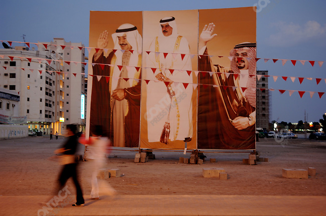 A couple of women walked past portraits of the King, Crown Prince and Prime Minister of Bahrain, all from the al Khalifa family, and one waved in return to the gesture of the pictures, Bahrain, December 18, 2005.