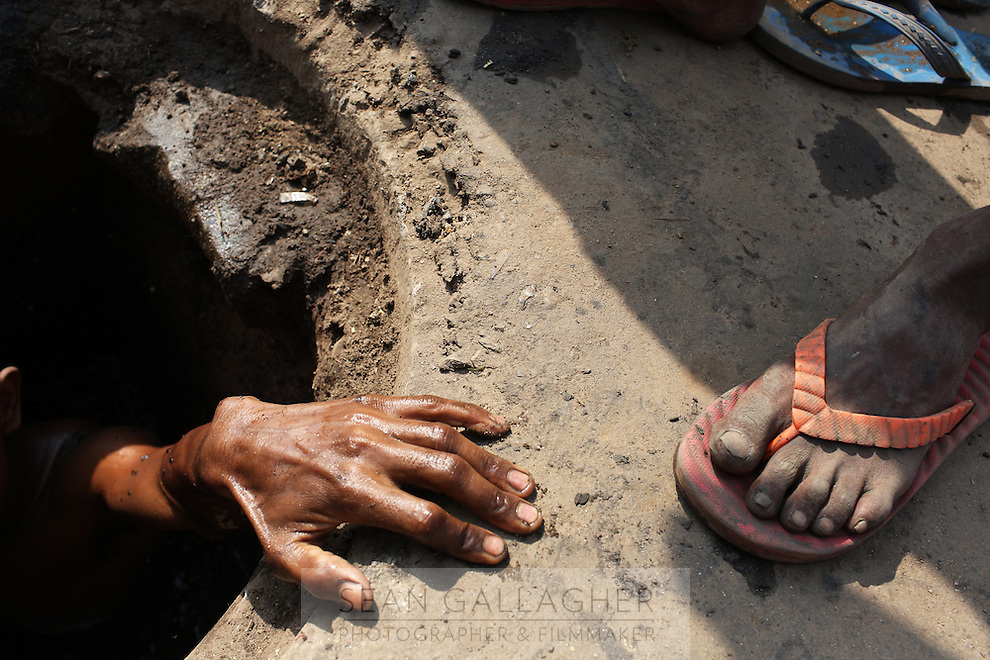 A worker's hand grabs the edge of a sewer drain in central Kolkata. The city's sewerage infrastructure is struggling to cope with an increasing population and subsequent usage demand. India. November, 2013