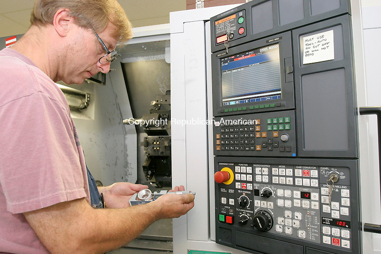 NEW MILFORD, CT-11 July 2005-071105TK11 Ronald Neumuller measures the lens holder of a microscope that formed with a Twin Spindle  CNC Turning Center. Tom Kabelka staff photo (Ronald Neumuller)CQ