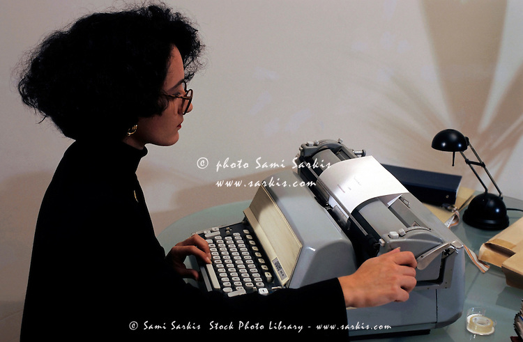 Portrait of a business woman typing on an old fashioned typewriter.