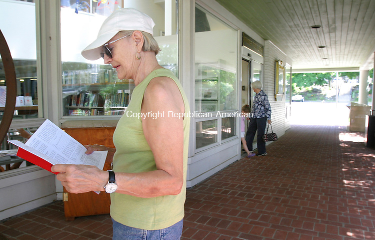 WOODBURY, CT. 30 June 2008-073008SV09--Eva Jasper of Woodbury stops to look at her book as she tries to make it to the library before it closes at noon in Woodbury Wednesday. The town is trying to close town building early this week to save money.<br /> Steven Valenti Republican-American