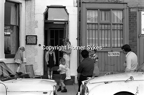 Familes talk and children play outside their bed anbd breakfast hotel, Blackpool, Lancashire 1974