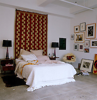 A large geometrically patterned wall hanging creates a focal point of the bed in the room