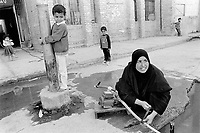 Iraq. Basra. Al Fao neighbourhood. A woman tapes the pipe used to collect clean water which will be sent to the flat by using the small engine. The woman wears the abaya and the hidjab (islamic headscarf) on her head to cover her hair. The abaya, sometimes also called aba, is a simple, loose over-garment, essentially a robe-like dress, worn by some women in parts of the Islamic world. Traditional abaya are black and may be either a large square of fabric draped from the shoulders or head or a long caftan. The abaya covers the whole body except the face, feet, and hands. The word hijab (or hidjab) refers to both the veil covering the head and traditionally worn by muslim women (Islamic headscarf), but also the  modest muslim styles of dress in general. Basra ( in arabic Al Basrah) is the capital of Basra Governorate in southern Iraq. 01.03.04 © 2004 Didier Ruef