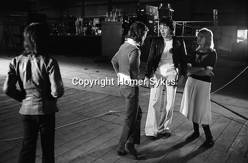 "Paul and Linda McCartney Wings Tour 1975. Paul and Linda talking to Denny Laine. They have just had an official Wings group photograph taken. Elstree rehearsal studio London England.. The photographs from this set were taken in 1975. I was on tour with them for a children's ""Fact Book"". This book was called, The Facts about a Pop Group Featuring Wings. Introduced by Paul McCartney, published by G.Whizzard. They had recently recorded albums, Wildlife, Red Rose Speedway, Band on the Run and Venus and Mars. I believe it was the English leg of Wings Over the World tour. But as I recall they were promoting,  Band on the Run and Venus and Mars in particular."