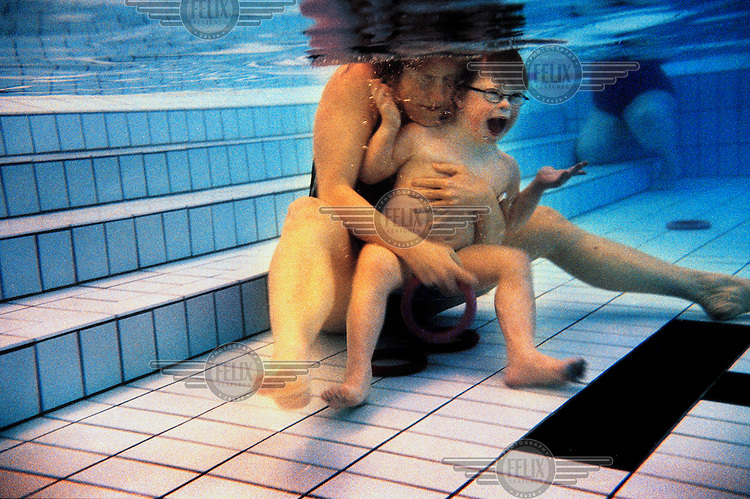 Jesper Nylund sits underwater with his mother in the swimming pool.  He enjoys swimming.  Six year old Jesper has Down Syndrome and although he is unable to talk, communicates through sign language.