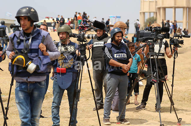 Palestinian journalists cover demonstrations on the Israel-Gaza border where Palestinians demanding the right to return to their homeland, in east of Gaza city on April 27, 2018. Photo by Atia Darwish
