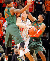 Virginia forward Evan Nolte (11) gets tangled up with Miami guard Rion Brown (15) and Miami guard Garrius Adams (25) during an NCAA basketball game Saturday Feb, 24, 2014 in Charlottesville, VA. Virginia defeated Miami 65-40.