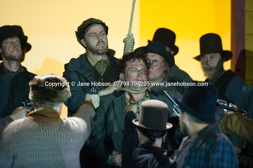 "London, UK. 30.09.2014. English National Opera's production of ""The Girl of the Golden West"", by Giacomo Puccini, directed by Richard Jones, conducted by Keri-Lynn Wilson, opens at London Coliseum. Picture shows: Peter Auty (Dick Johnson - in noose). Photograph © Jane Hobson."