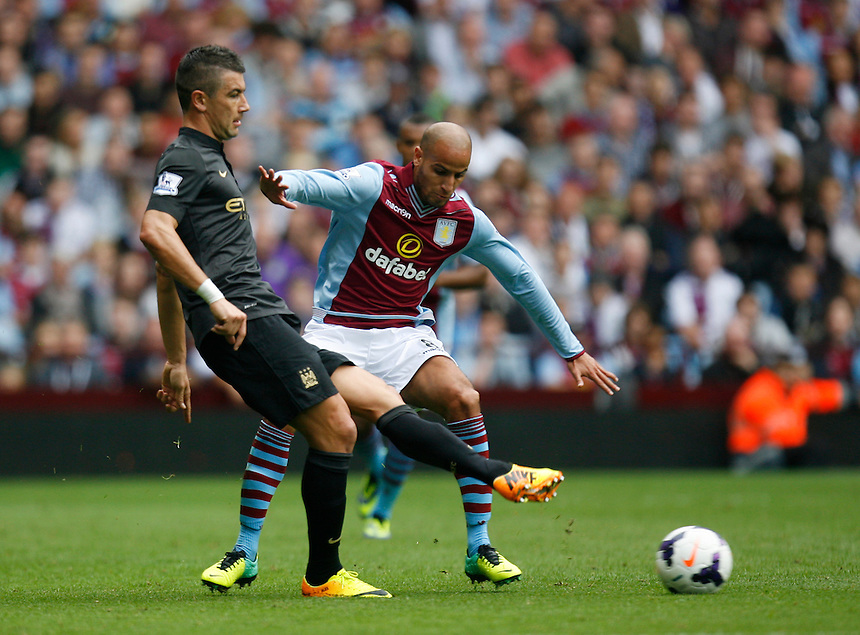 Manchester City's Aleksandar Kolarov (L) and Aston Villa's Karim El Ahmadi in action during todays match  <br /> <br /> Photo by Jack Phillips/CameraSport<br /> <br /> Football - Barclays Premiership - Aston Villa v Manchester City - Saturday 28th September 2013 - Villa Park - Birmingham<br /> <br /> &copy; CameraSport - 43 Linden Ave. Countesthorpe. Leicester. England. LE8 5PG - Tel: +44 (0) 116 277 4147 - admin@camerasport.com - www.camerasport.com