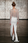 Model walks runway in a fully beaded long sleeve jewel neck top with side drape back slit skirt, from Inbal Dror Fall 2018 bridal collection on October 5, 2017; during New York Bridal Fashion Week.