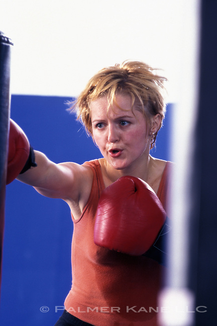 Woman working out with heavy punching bag